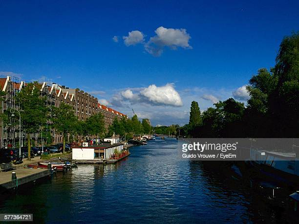 Canal Amidst Buildings And Trees Against Blue Sky
