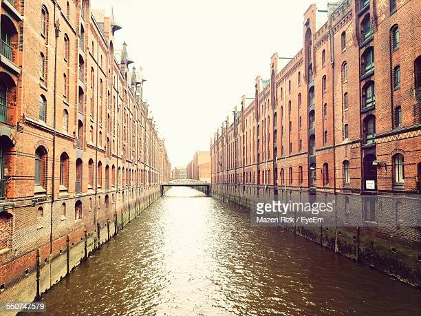 Canal Amidst Historic Warehouses Against Clear Sky At Speicherstadt