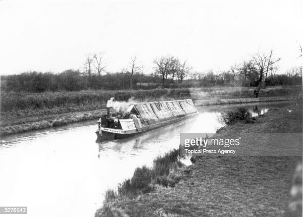 A canal barge moving along the Grand Union Canal near Crick Rugby