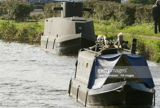 A canal barge sails past a barge transformed into a German UBoat on the LeedsLiverpool canal in Botonay Bar near Chorley Lancashire