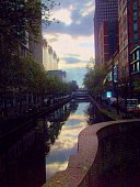 Canal Between Buildings Against Cloudy Sky At Dusk