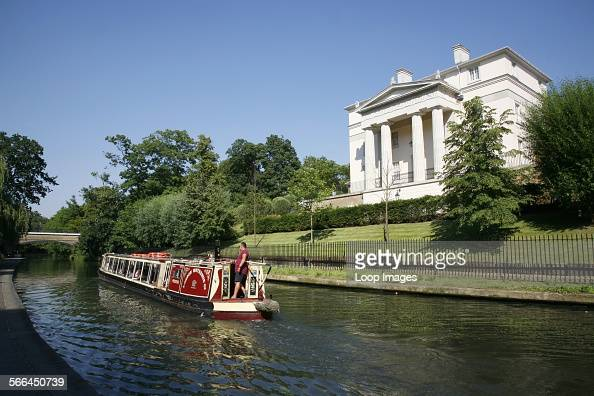 Canal boat on Regent's Canal passing a recent Quinlan Terry designed neoClassical villa in Regent's Park