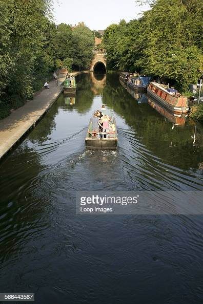 A canal boat sailing up the Regents Canal towards the Islington Tunnel
