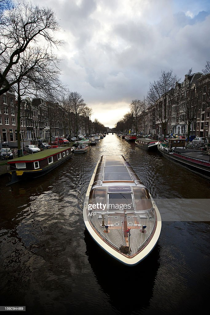 A canal boat sails on January 10, 2013 on the Keizersgracht, one of the city of Amsterdam's three main canals. 2013 will mark the 400th anniversary since construction began on Amsterdam's world renowned Canal Ring that was added to the UNESCO World Heritage list. AFP PHOTO / ANP / JERRY LAMPEN -- The Netherlands out --