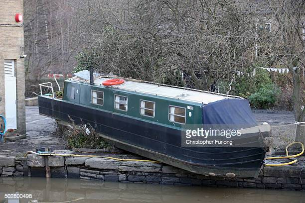 Canal boats are left beached and sunk after flood waters from the River Calder overflowed into the Calder and Hebble Canal creating a raging flow...