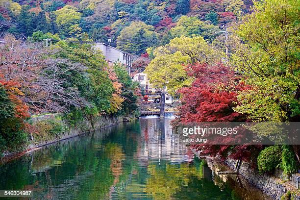 Canal in Arashiyama lined with autumn foliage