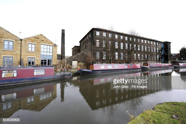 Canal pleasure boats moored for the winter on the Leeds and Liverpool canal alongside old mills at Silsden near KeighleyWest Yorkshire today awaiting...
