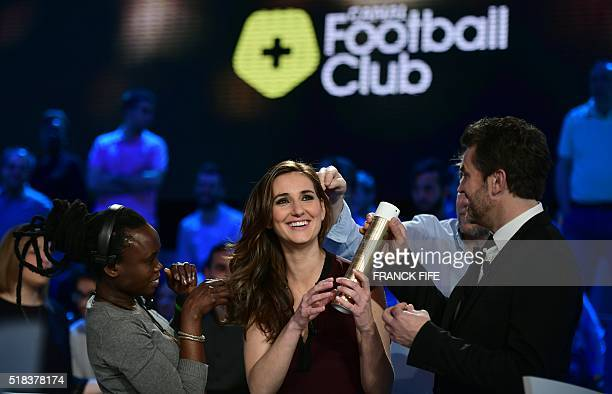 Canal Plus Journalist Marie Portolano jokes with sports journalist and show host Herve Mathoux before the TV show 'Canal Football Club' on March 27...