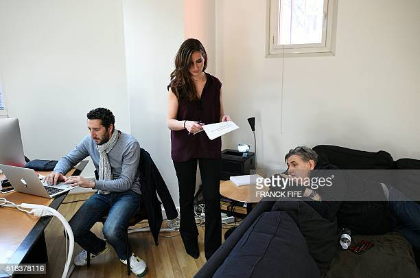 Canal Plus Journalist Marie Portolano works as sport journalist Pierre Menes relax prior to the start of the TV show 'Canal Football Club' on March...