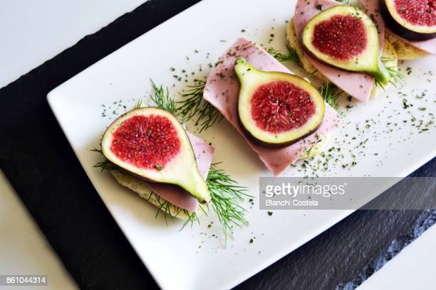 Canapes of fresh cheese ham and figs in trays on a black table