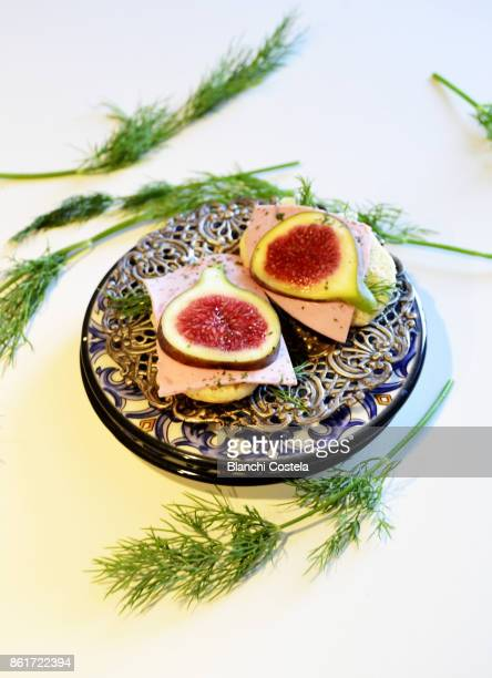 Canapes of fresh cheese ham and figs in white background