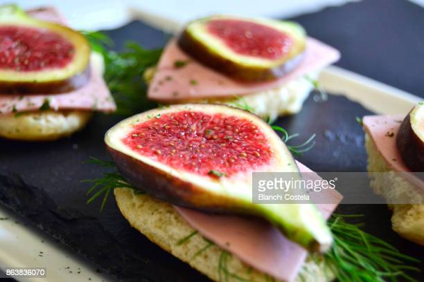 Canapes of fresh cheese ham and figs
