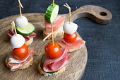 canapés with ham and tomatoes on wooden Board