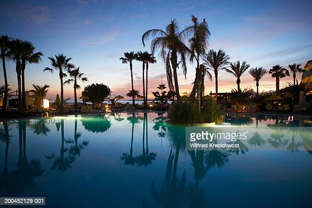 Canary Islands, Lanzarote, swimming pool and palm trees, sunset