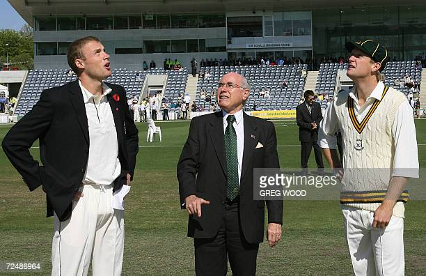 England cricket captain Andrew Flintoff and PM's XI captain Cameron White watch as Australian Prime Minister John Howard tosses the coin prior to the...
