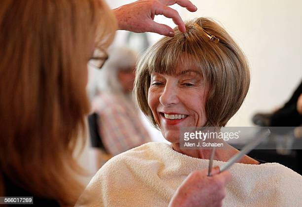 Cancer patient Carol Hekman right reacts with an approving smile as Jose Eber Salon stylist Lisanne Messinger left right trims and adjusts her new...