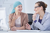 Smiling cancer patient talking to her doctor