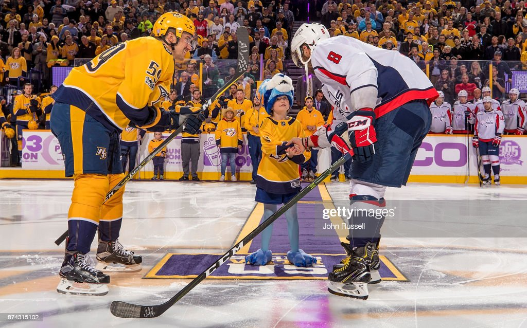 Cancer survivor Andie Owen shakes hands with Alex Ovechkin #8 of the Washington Capitals and Roman Josi #59 of the Nashville Predators after dropping the puck on Hockey Fights Cancer night at Bridgestone Arena on November 14, 2017 in Nashville, Tennessee.