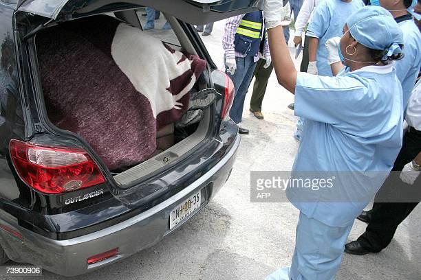 Peritos de la Procuraduria de Justicia del estado de Quintana Roo revisan el 16 de abril de 2007 uno de los cinco cuerpos encontrados en un vehiculo...