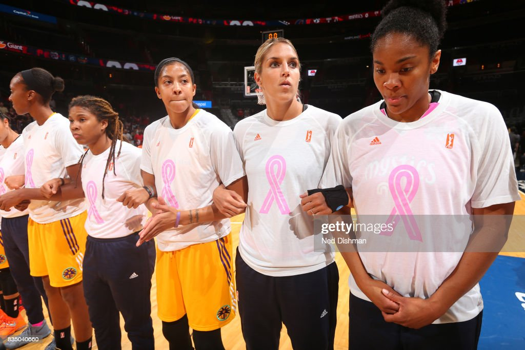 Candace Parker #3 of the Los Angeles Sparks locks arms with Elena Delle Donne #11 of the Washington Mystics during the national anthem on August 16, 2017 at the Verizon Center in Washington, DC.