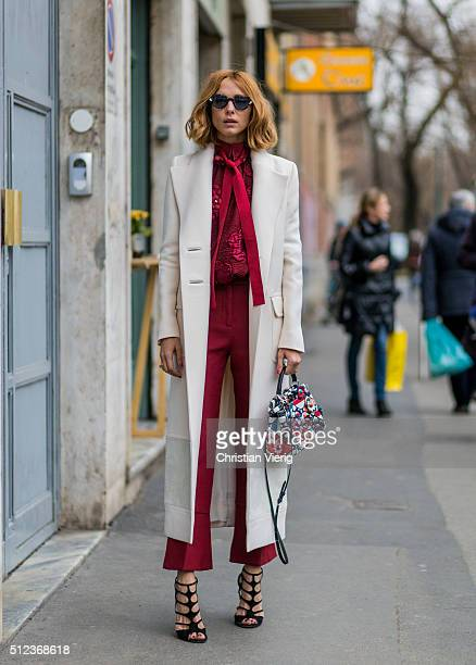 Candela Novembre wearing a long creme coat a red blouse and pants and bag all Fendi seen outside Fendi during Milan Fashion Week Fall/Winter 2016/17...