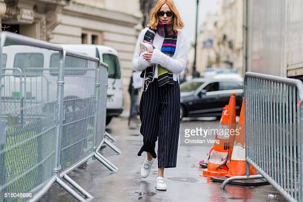Candela Novembre wearing a white wool sweater scarf and black white striped pants outside Moncler Gamme Rouge during the Paris Fashion Week...