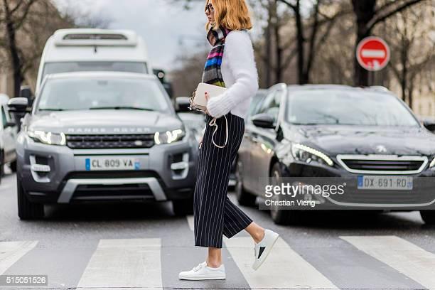 Candela Novembre wearing a white wool sweater white sneaker and black white striped pants outside Miu Miu during the Paris Fashion Week Womenswear...