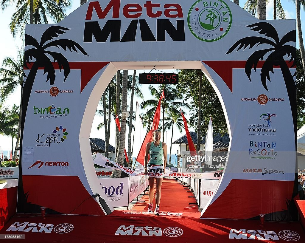 Candice Hammond of New Zealand reaches the finish line in third place during the Meta Man Iron Distance Triathlon on August 31, 2013 in Bintan Island, Indonesia.