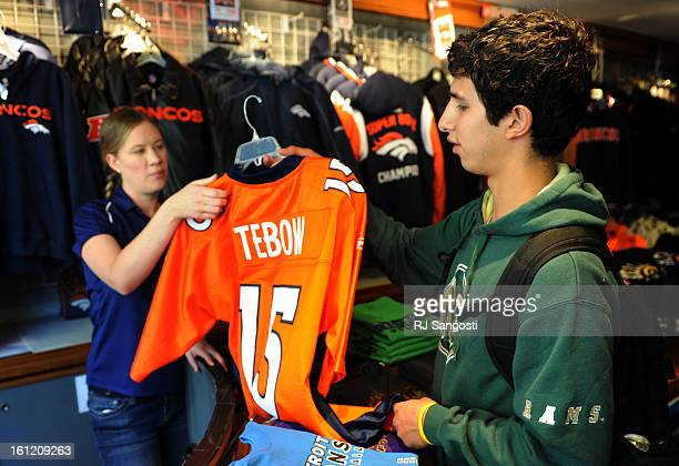 Candice King left who works at at Sportsfan on the 16th Street Mall in downtown Denver hands a Tim Tebow jersey to Bronco fan Willy Aragon Tuesday...