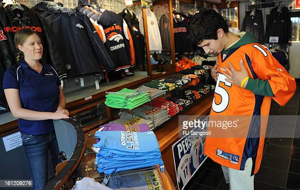 Candice King left who works at at Sportsfan on the 16th Street Mall in downtown Denver watches as Bronco fan Willy Aragon Tuesday Oct 11 as he tries...