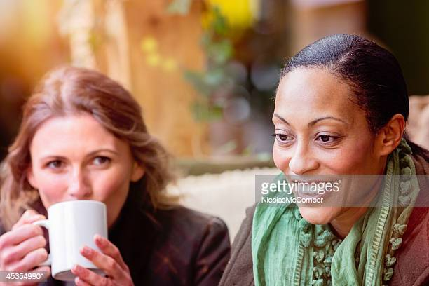 Candid friendship moment between two women on coffee break