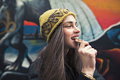 candid image of a beautiful young woman biting a chocolate bar