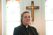 Candid of real female pastor inside church with cross in background.