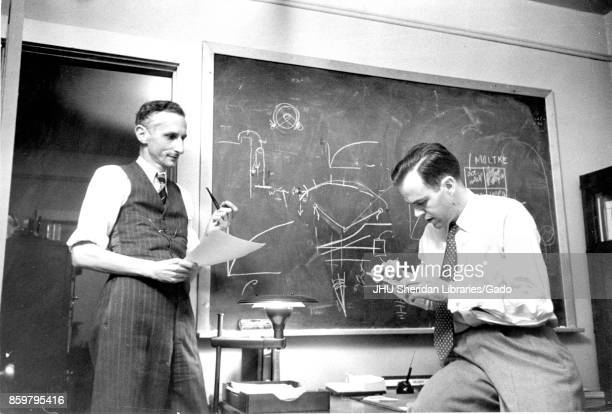 Candid of two men in a Johns Hopkins University classroom in front of a blackboard covered in mathematical equations including James Herbert Henry...