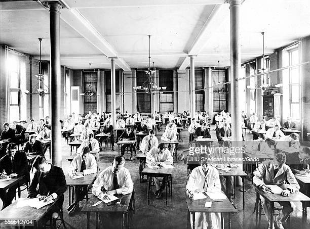 Candid photograph of students wearing suits sitting at desks taking an exam in a open room with tall windows and chandeliers at Johns Hopkins...