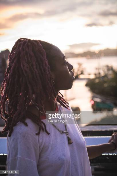 A candid portrait of a young, African American woman enjoying a sunset.