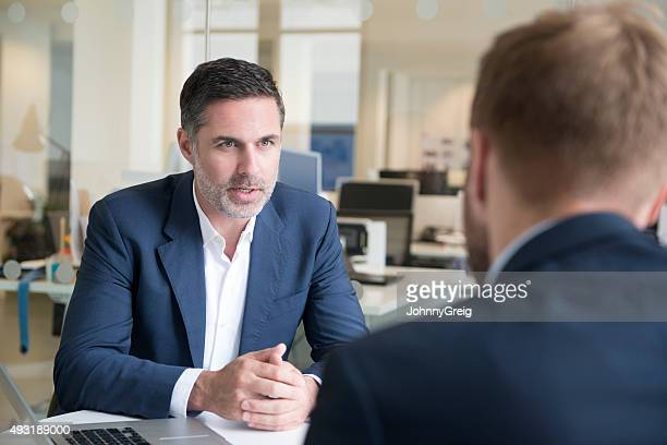 Candid portrait of businessman talking to colleague