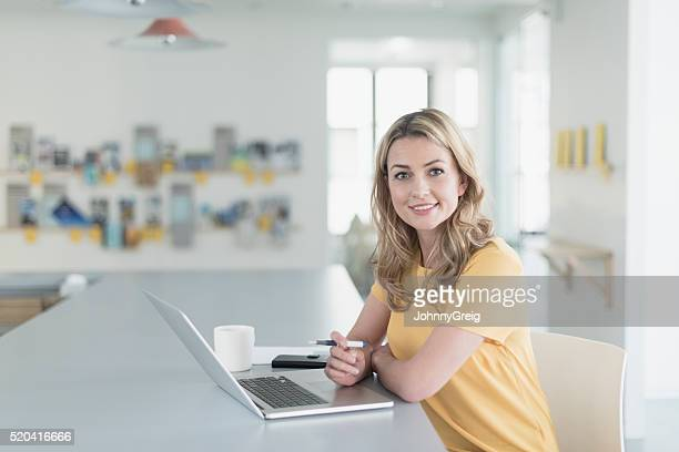 Candid portrait of businesswoman smiling towards camera with laptop