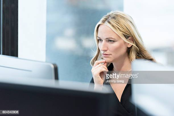 Candid portrait of businesswoman using computer in offcie