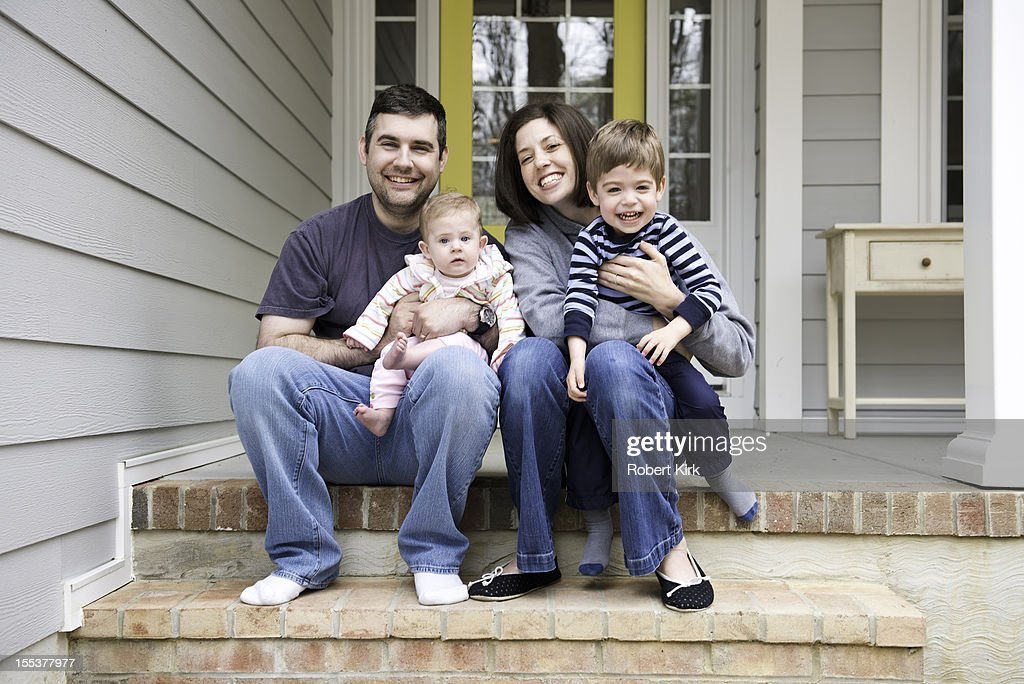 Candid portrait of family sitting on front porch stairs