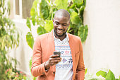 Young African man in orange jacket using smartphone. Young happy Ethnic man texting on phone. Cheerful casual male reading text message.