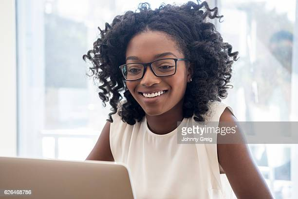 Candid portrait of young African businesswoman using computer, smiling