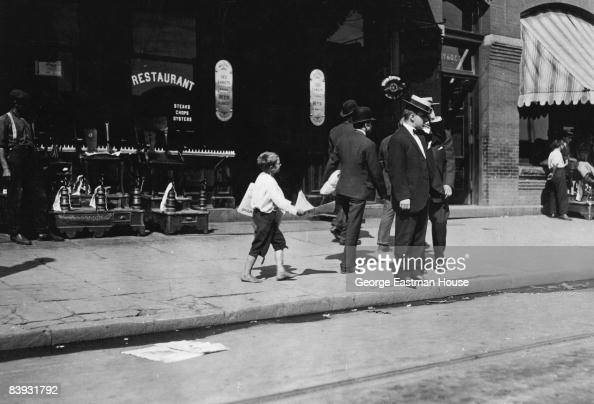 Candid shot of Newsie selling papers to men passing by along the street 1912