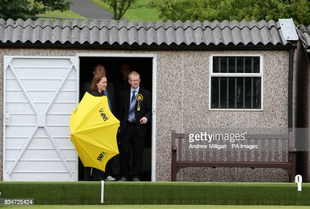 SNP candidate for Glasgow East John Mason with First Minister Alex Salmond taking shelter while visiting Garrowhill Bowling Club to highlight support...