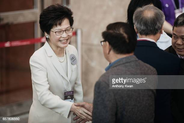 Candidate for Hong Kong's chief executive and former chief secretary Carrie Lam greets a memeber of election committee outside a polling station for...