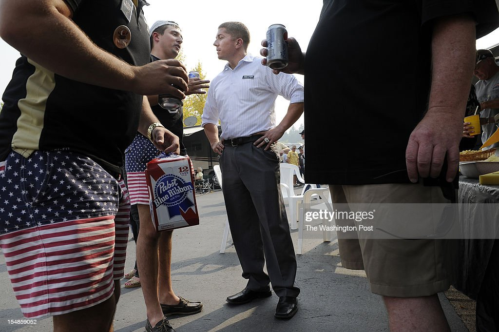 Candidate for the U.S. House of Representatives, Jimmy Farris, center, talks with Miles Starr, left center, as Eric Taylor, left, and Bob Wetherell, right, stand close by as Farris greets potential voters before a football game at the University of Idaho in Moscow, ID on Saturday September 22, 2012. Jimmy is a former professional football player, who played with the Washington Redskins among other teams. He was a member of the New England Patriots when they won Super Bowl XXXVI. He grew up in Lewiston, ID.