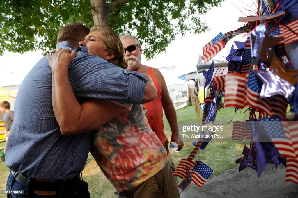 Candidate for the U.S. House of Representatives, Jimmy Farris, left, is hugged Althea Zielinski, left center, as her husband, Bill Zielinski, center, looks on as Farris greeted people from a booth he was sharing with other candidates at the Nez Perce County Fair on Friday September 21, 2012 in Lewiston, ID. Jimmy is a former professional football player, who played with the Washington Redskins among other teams. He was a member of the New England Patriots when they won Super Bowl XXXVI. He grew up in Lewiston, ID.