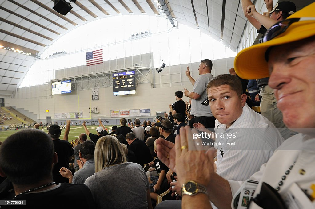 Candidate for the U.S. House of Representatives, Jimmy Farris, right center, looks over at family friend, Steve Rice, right, as they take in a University of Idaho football game in the Kibbie Dome as Farris campaigned at the university in Moscow, ID on Saturday September 22, 2012. Jimmy is a former professional football player, who played with the Washington Redskins among other teams. He was a member of the New England Patriots when they won Super Bowl XXXVI. He grew up in Lewiston, ID.