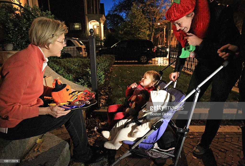 Candidate for U.S. Senate Elizabeth Warren hands out candy to trick-or-treaters Ella, 2, Jackie, 5 months, and mother Kathrin Vandenberghe at her Cambridge home on Halloween.