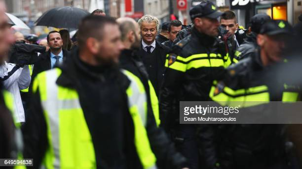 Candidate Geert Wilders is guarded by police after he speaks to the crowd hands out pamphlets or flyers and poses for selfies on his election...